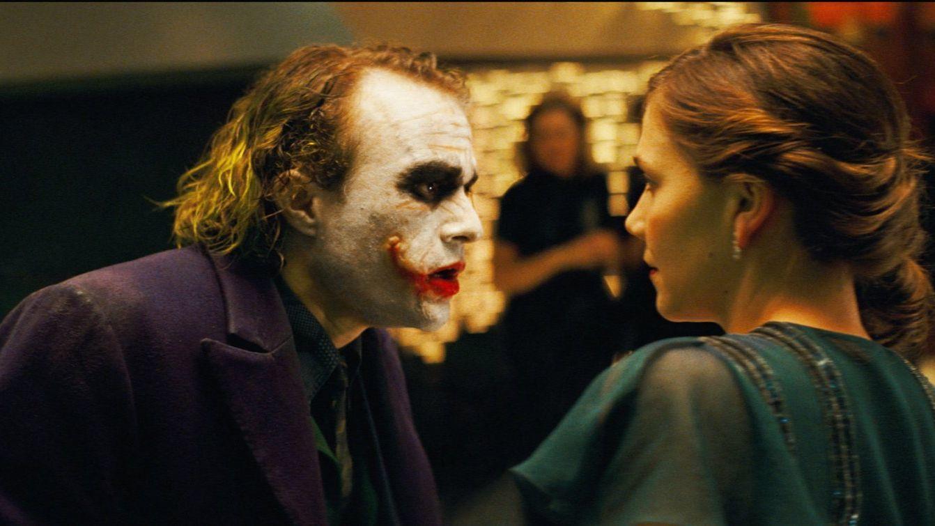 Nolan szándékoltan nem mutatta meg Jokert teljes sminkben és jelmezben a többi színésznek, így azok abban a jelenetben szembesültek vele először, amikor Bruce Wayne jótékonysági partit ad. Michale Caine annyira ledöbbent a látványon és Ledger előadásán, hogy elfelejtette a szövegét, a Maggie Gyllenhaal arcán látható undorral vegyes félelem pedig teljesen valós. (Warner Bros.)