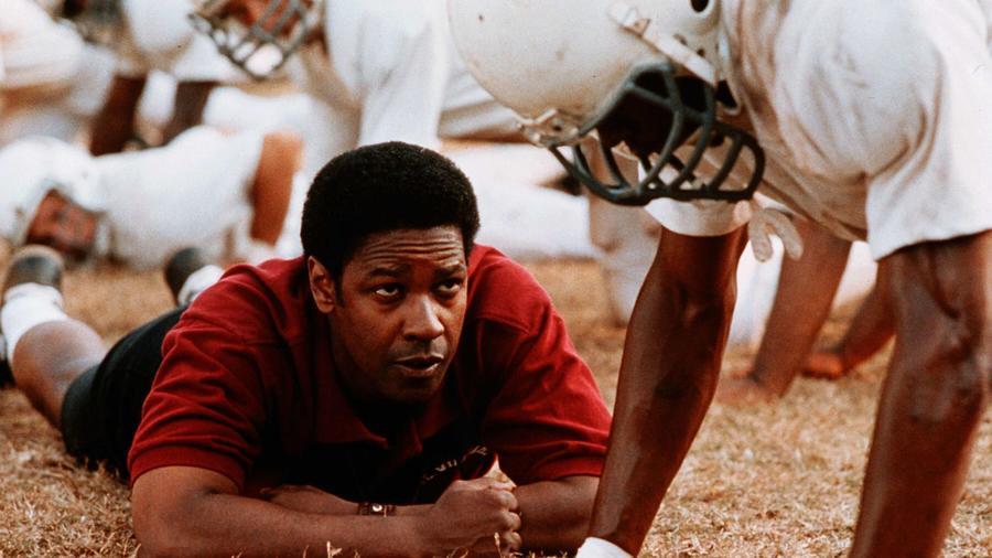 Minden idők egyik legszuggesztívebb amerikai focis filmje. Az igaz történet 1971-ben a virginiai Alexandria városában játszódik, ahol a faji szegregáció megszüntetésével összevonják a feketék és fehérek gimis csapatait a T.C. Williams középiskolában. Edzőjük pedig egy fiktív fekete karakter, Herman Boone lesz, aki nagyot küzd az elfogadásért. Denzel Washington egyszerűen zseniális! (Tracy Bennett/Walt Disney/Bruckheimer/Kobal/Shutterstock)