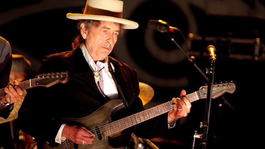 """Bob Dylan az 1998-as Grammy díjátadón próbálta eljátszani Love Sick című számát, azonban előadását egy félmeztelen fickó szakította meg, mellkasán Soy Bomb (""""Szójabomba"""") felirattal, majd vicces táncot lejtett. Fura és zavarba ejtő pillanat volt, ami talán Dylan egész munkásságára jellemző (gondoljunk csak a soha fel nem vett Nobel-díjára). (REX/ Shutterstock)"""