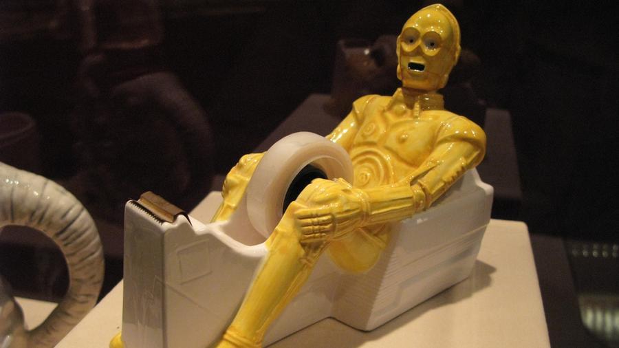 """Kíváncsiak lennénk a folyamatra, melynek során valaki elméjében megszületett ennek a tárgynak az ötlete, és azt mondta: """"Igen, és akkor húzzuk ki a ragasztót C-3PO sliccéből!""""(filmsfix.com)"""