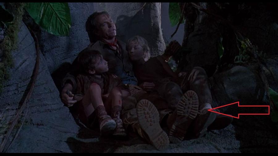 Amikor Grant és a gyerekek fent vannak a fán és Tim viccet mesél a kamera kicsit többet mutat a tájból, és (hoppá) Grant csizmájából, ami teljesen tiszta. Ez persze lehetetlen lenne, hiszen eddig kutyagoltak a sárban, a nedves aljnövényzetben. (Universal Pictures)