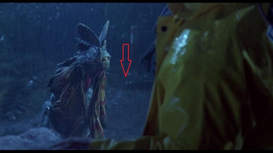 Amikor a Dilophosaurus kinyitja a ketrecet, látszik az ajtót nyitó kötél. (Universal Pictures)